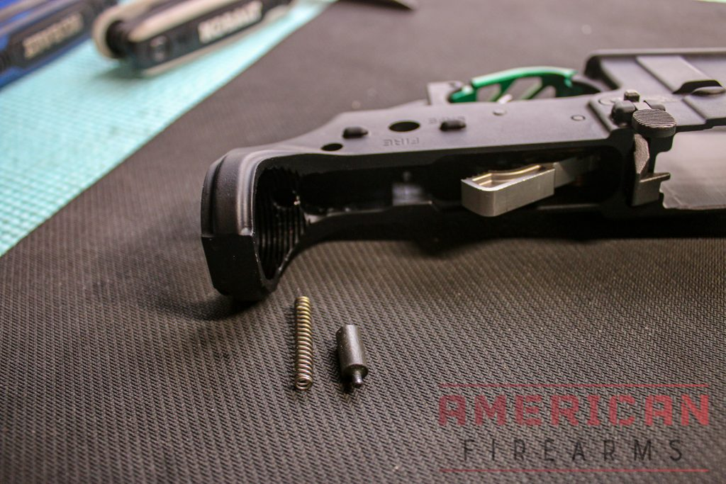 In the lower receiver, put the buffer tube retainer spring into the hole and the buffer retainer on top of it.